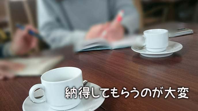 机の上に資料を置いて話し合うお客とコーディネーター