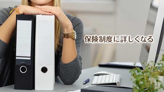ファイリングケースを机の上に置く事務員の女性