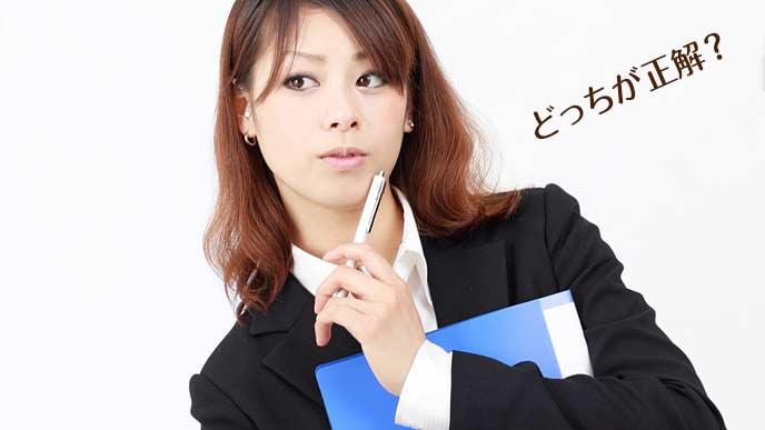 ペンを顎先に当てながら悩む女性事務員