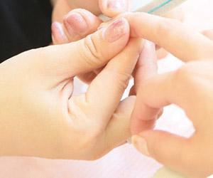 爪の状態を調べるネイリスト