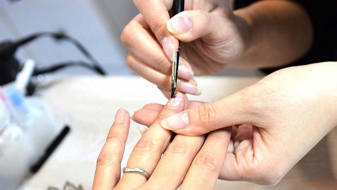 女性客の爪にマニュキアを塗るネイリスト