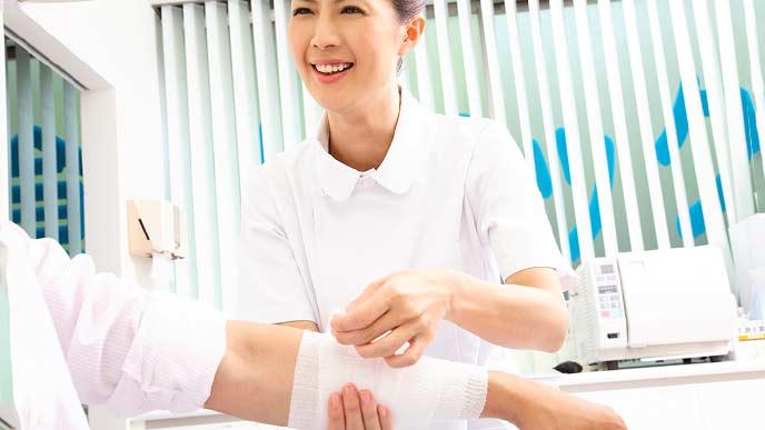患者の腕に包帯を巻く看護師
