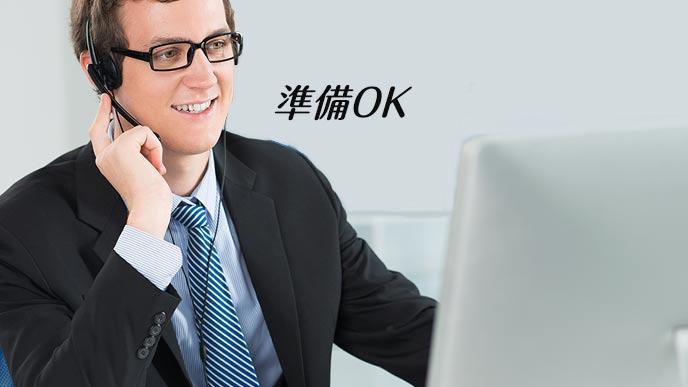 パソコンの前で背広を着てインカムを着ける男性