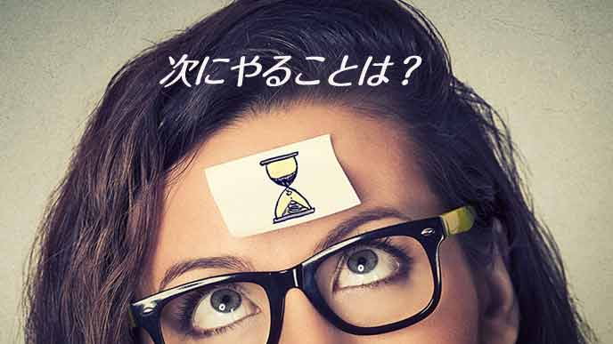 額に貼った砂時計を気にする女性
