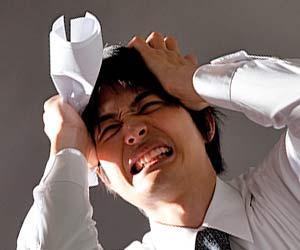 不採用の書類を持って頭を抱える男性