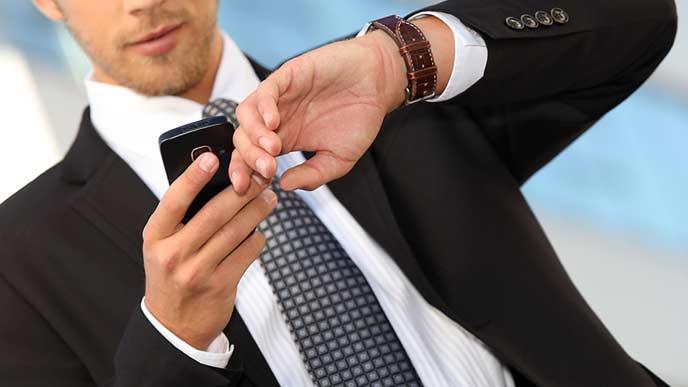 スマホと腕時計を一緒に見るビジネスマン