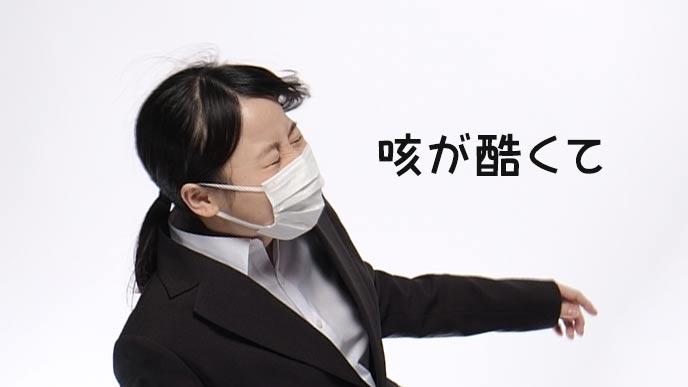 マスクをして咳をする女学生