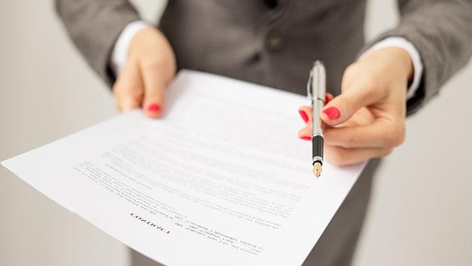 書類とペンと差し出す転職エージェント
