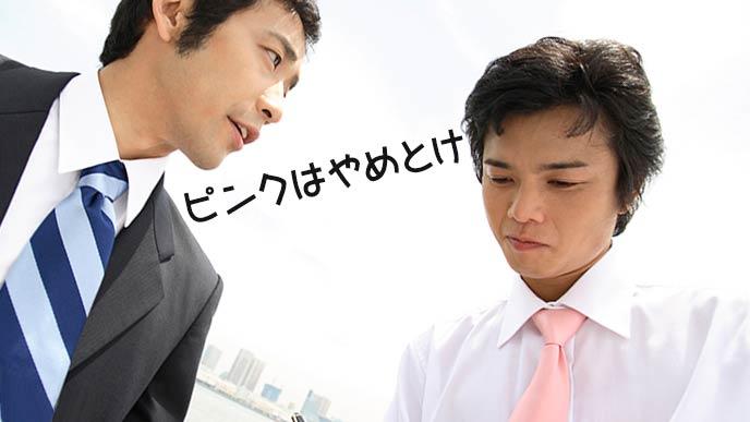 ピンクのネクタイした男性に先輩が忠告する