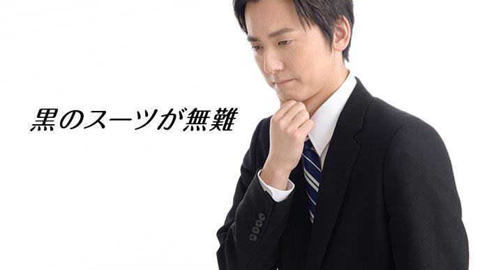 黒のスーツを着て顎に手をやる就活学生
