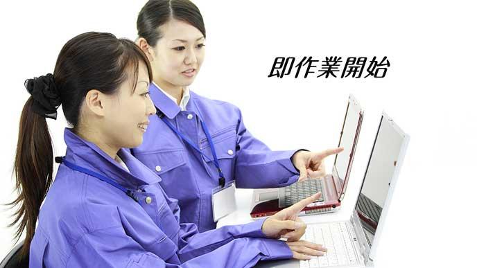 作業着でパソコンを操作する派遣社員