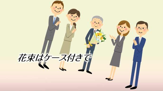 花束を持って同僚に囲まれる退職者