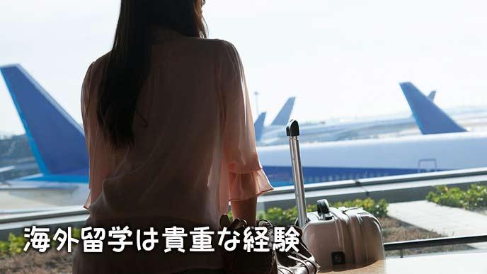 空港の待合室で外を眺める女性