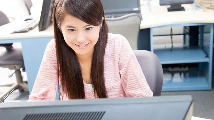 大学のパソコンで調べものをする女学生