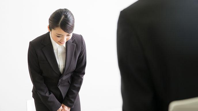 スーツ姿の女性が面接官に挨拶する