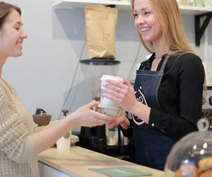 コーヒーを手渡す女性販売員