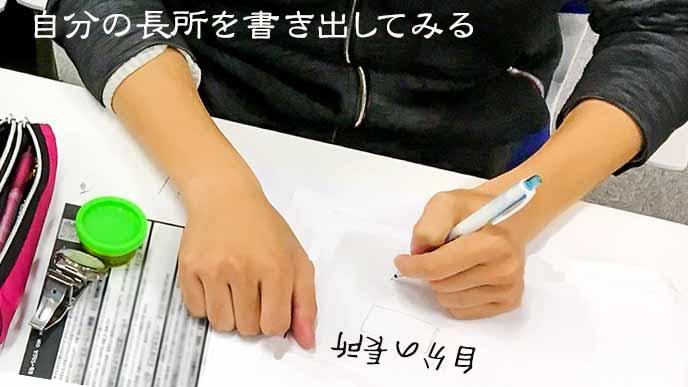 自分の長所を紙に書き出す学生