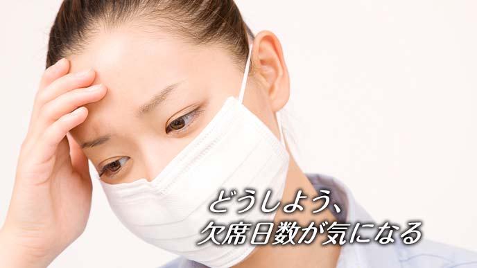 マスクをして額に手を触れる女性