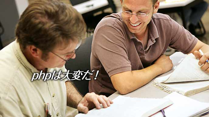 プログラムの教本を見て互いに勉強する年配の男性