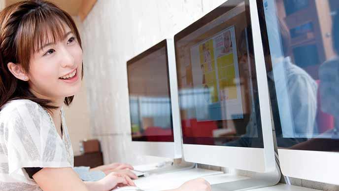 モニター画面を見ながらグラフィック制作をする女性