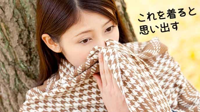 ストールで顔を隠す女性