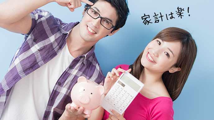 夫婦並んで貯金箱と電卓を持つ