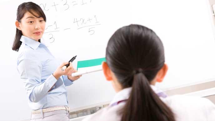 生徒に勉強を教える塾講師
