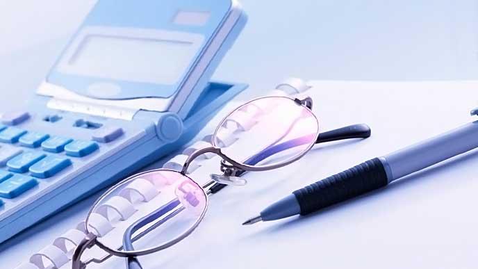 電卓とビジネス用のノートの上に置かれた眼鏡とボールペン