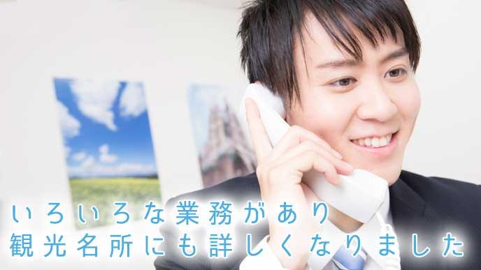 お客様との電話対応をする旅行代理店の男性スタッフ