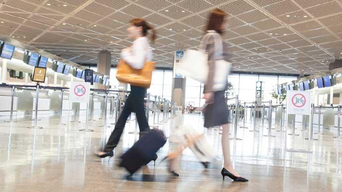 海外出張で空港のロビーを歩くビジネスウーマン