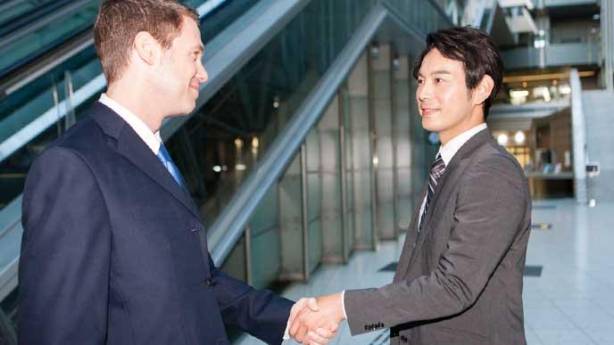海外出張先での仕事で取引相手と握手をする日本人ビジネスマン