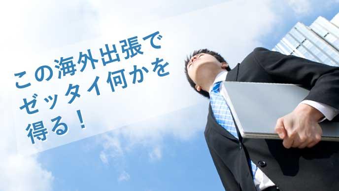 空を高く見上げ「海外出張で何かを得る!」と誓う向上心の高いビジネスマン