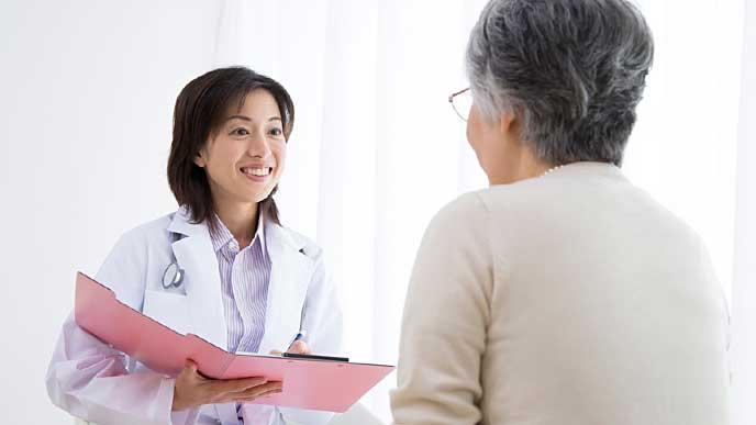 患者の老人を診察する保健師