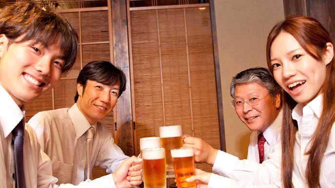 職場の飲み会にビールで乾杯をする会社員