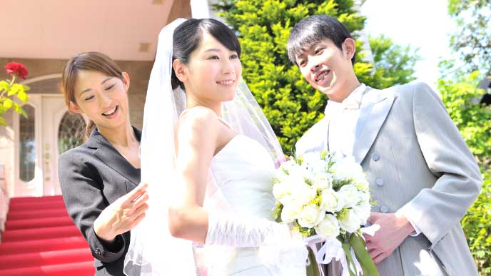 結婚式場で新婦のドレスを手入れをするウエディングプランナー