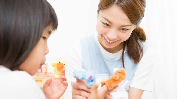 子供の遊び相手をしている幼稚園教諭