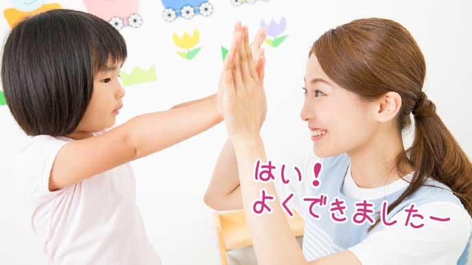 子供をハイタッチして褒める幼稚園教諭