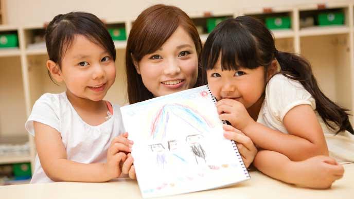 子供と一緒にクレヨンで描いた絵を見せる幼稚園教諭