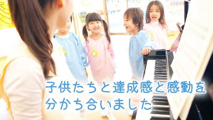 ピアノを弾いて子供達と一緒に歌う幼稚園教諭