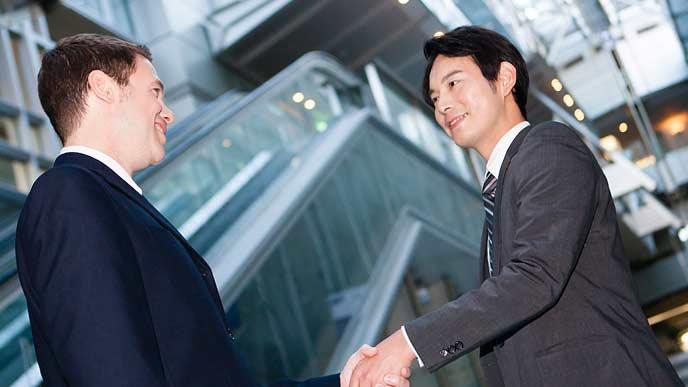 外人社員と日本人が握手する