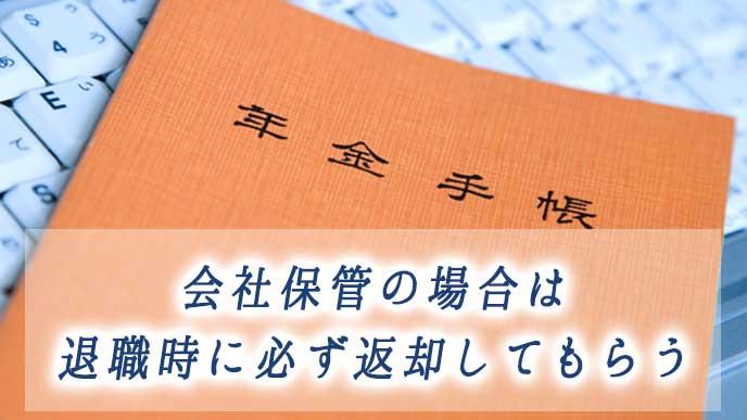 会社のノートパソコンの上に置かれた年金手帳