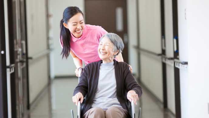 車椅子に乗った老人を介護するヘルパー