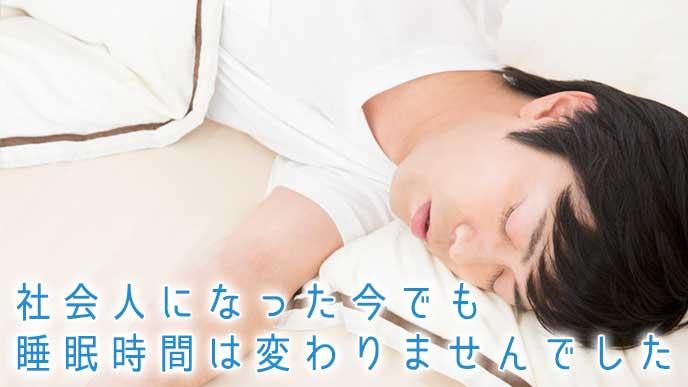 ベッドの上で睡眠をとる社会人の男性