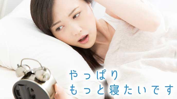 目覚まし時計に起こされる睡眠不足の女性