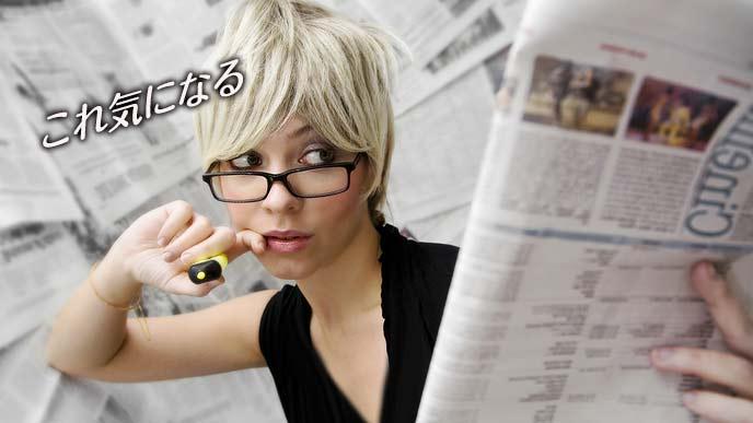 蛍光ペンを持って新聞を斜めに見つめる女性