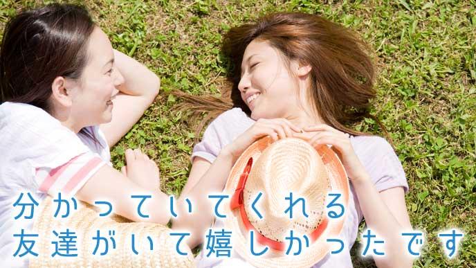 友達と一緒に野原で仲良く寝ころぶ女性