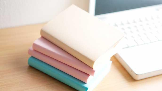 机に積みあがった就活用の書籍とパソコン