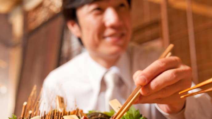 宴会の席で料理を食べるビジネスマン