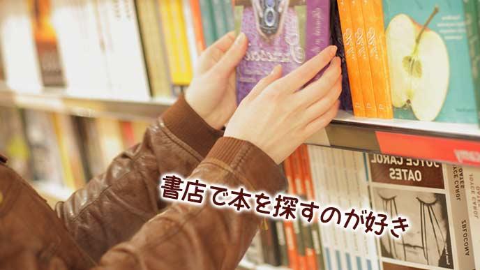 書棚から本を選び出す男性