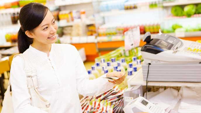 スーパーのレジで品物を買う女性